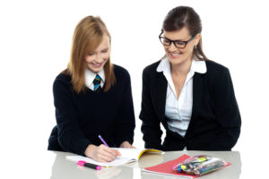 Teacher assisting schoolgirl in her homework